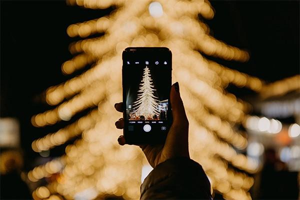 persoon maakt foto van kerstboom met lichtjes