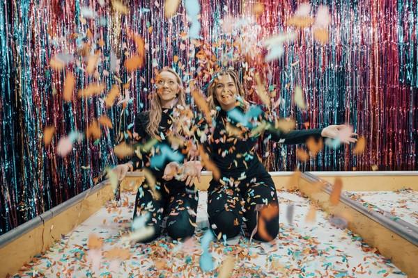 Twee vrouwen die gooien met confetti