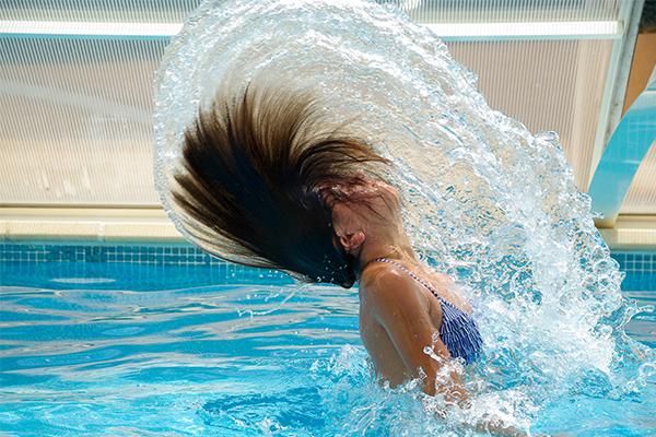 mevrouw in zwembad doet water hair flip