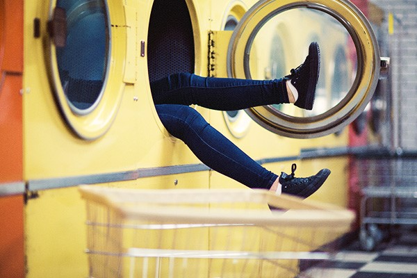 persoon die met benen uit wasmachine steekt