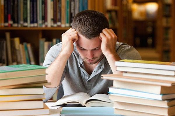 mannelijke student tussen de studieboeken is aan het studeren